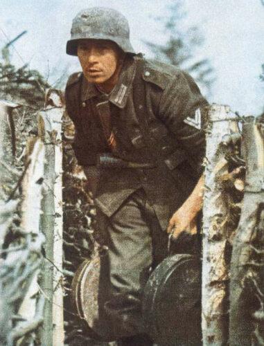 """Из пропагандистского журнала """"Сигнал"""". Обер-ефрейтор в окопе на передовой с двумя противотанковыми минами """"T-Mine 42""""."""