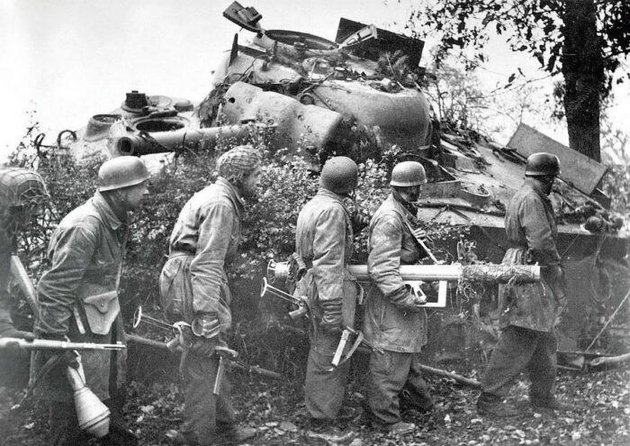 """Западный фронт 1944 г. Десантники вермахта на фоне подбитого танка """"Шерман"""". Вооружение: карабин К98k, автоматы МР40 и гранатометы """"Панцерфауст"""" и """"Офенрор"""" (Ofenrohr)."""
