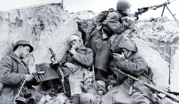 Короткий перерыв. Красноармейцы принимают пищу. Солдат с пулеметом в охранении